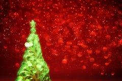 A árvore de Natal de incandescência e as luzes vermelhas abstraem o backgro Fotos de Stock