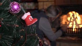 Árvore de Natal decorada com o homem superior perto da chaminé no fundo vídeos de arquivo