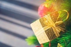 Árvore de Natal decorada com suspensão da caixa dourada foto de stock