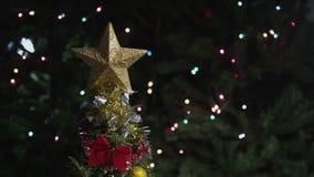 Árvore de Natal Defocused com estrela e as lanternas elétricas coloridas video estoque
