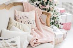 A árvore de Natal do aconchego do Natal, descansos em um sofá empluma-se a cobertura cor-de-rosa do véu do fio grosso, cosiness d Imagem de Stock Royalty Free