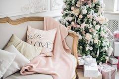A árvore de Natal do aconchego do Natal, descansos em um sofá empluma-se a cobertura cor-de-rosa do véu do fio grosso, cosiness d Foto de Stock