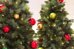 A árvore de Natal dois decorou luzes e bolas das agulhas do pinho foto de stock