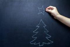 A árvore de Natal e a mão do ` s da criança com a estrela no quadro-negro abstraem o fundo Foto de Stock