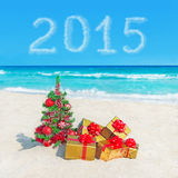 A árvore de Natal e os presentes dourados no mar encalham Conceito para o YE novo Imagem de Stock Royalty Free