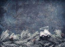 Árvore de Natal em passeios do carro do brinquedo em ramos do abeto no fundo azul dar, cartão do feriado com espaço da cópia fotografia de stock royalty free