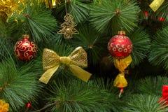 Árvore de Natal em um equipamento rico vermelho e do ouro com bolas e uma BO imagens de stock royalty free