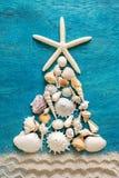 Árvore de Natal feita do tipo diferente de escudos e de estrela do mar do mar com a decoração da areia no fundo de madeira azul,  foto de stock royalty free