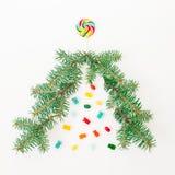 Árvore de Natal feita de ramos do abeto e de doces coloridos brilhantes no fundo branco Conceito do feriado Configuração lisa, vi Fotos de Stock