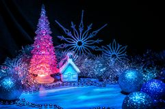 Árvore de Natal gelada que incandesce com luz cor-de-rosa em um fundo azul foto de stock royalty free