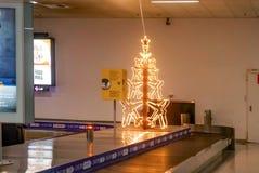 Árvore de Natal iluminada do avião na correia transportadora da bagagem no aeroporto tarde quase abandonado na noite no Ch fotografia de stock