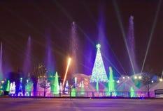 Árvore de Natal iluminada, jatos da água e árvores coloridas dos feriados na noite na área internacional da movimentação foto de stock royalty free