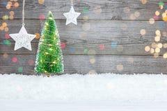 Árvore de Natal iluminada na neve e estrelas brancas contra o cinza Fotos de Stock Royalty Free