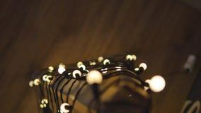 Árvore de Natal de madeira Festão das luzes Estilo do vintage Fundo de ampolas em um campo no borrão do resto vídeos de arquivo