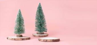 Árvore de Natal na fatia de madeira do log com a caixa atual no rosa pastel foto de stock royalty free