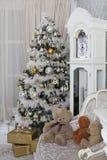 Árvore de Natal na véspera do ` s do ano novo em uma sala branca com presentes do Natal Foto de Stock