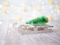 Árvore de Natal no trenó do brinquedo Cartão do Natal e do ano novo no fundo de madeira Imagem de Stock Royalty Free