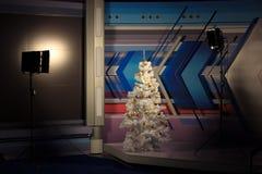 Árvore de Natal no vídeo do estúdio, leve em ambos os lados Árvore do White Christmas com brinquedos do ouro Decoração do escritó imagem de stock