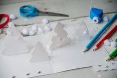 Árvore de Natal de papel criativa na folha do Livro Branco, nas tesouras e em pastéis coloridos no fundo da tabela de cor Foto de Stock