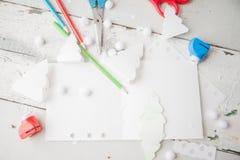 Árvore de Natal de papel criativa na folha do Livro Branco, nas tesouras e em pastéis coloridos no fundo da tabela de cor Fotografia de Stock