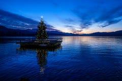 Árvore de Natal que flutua em um lago após o por do sol Fotografia de Stock