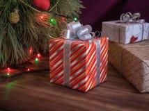 A árvore de Natal verde decorada com brinquedos e festão conduziu luzes Encaixota presentes Imagens de Stock