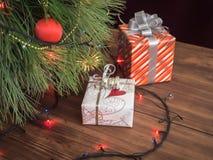 A árvore de Natal verde decorada com brinquedos e festão conduziu luzes Encaixota presentes Foto de Stock