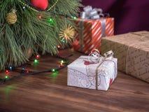 A árvore de Natal verde decorada com brinquedos e festão conduziu luzes Encaixota presentes Fotografia de Stock