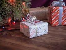 A árvore de Natal verde decorada com brinquedos e festão conduziu luzes Encaixota presentes Imagem de Stock
