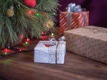 A árvore de Natal verde decorada com brinquedos e festão conduziu luzes Encaixota presentes Fotos de Stock