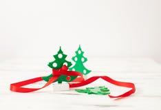 Árvore de Natal verde pequena com a fita vermelha no branco Fotos de Stock