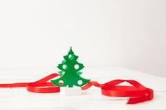 Árvore de Natal verde pequena com a fita vermelha no branco Foto de Stock Royalty Free