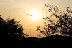 A árvore e a casa da transmissão da tevê da silhueta com o sol imagem de stock
