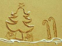 A árvore e os doces de Natal colam o desenho na areia Fotos de Stock