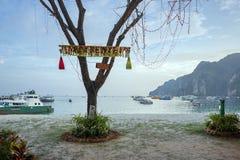 A árvore está na costa, decorada pelo ano novo, na perspectiva do mar com barcos fotografia de stock