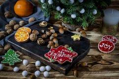 A árvore, a laranja, as fatias alaranjadas e os flocos de neve dos biscoitos encontram-se na tabela de madeira imagem de stock