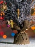 Árvore pequena do Xmas da tabela que está na neve, com luzes da árvore de Natal, fundo do bokeh e espaço da cópia Imagens de Stock Royalty Free