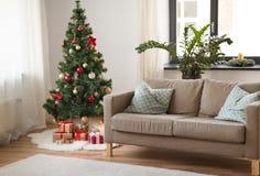 Árvore, presentes e sofá de Natal na casa acolhedor imagens de stock royalty free