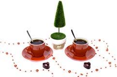 Árvore vermelha de duas xícaras de café e uma cesta do chocolate Imagens de Stock