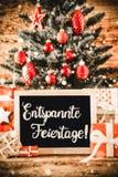 A árvore vertical, presentes, caligrafia Entspannte Feiertage significa o Feliz Natal imagens de stock