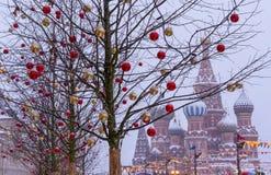 Árvores decoradas com os brinquedos do Natal na perspectiva da catedral da manjericão do St moscow kremlin foto de stock
