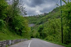 Árvores que cercam uma volta da estrada da montanha abaixo do céu épico com nuvens imagem de stock royalty free