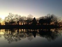 Árvores que refletem na superfície da água durante o por do sol no inverno Foto de Stock Royalty Free