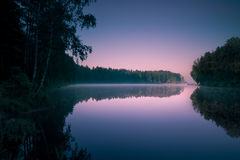 Árvores que refletem na superfície lisa da água no nascer do sol Fotografia de Stock
