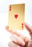 Ás dourado em uma mão Fotografia de Stock Royalty Free