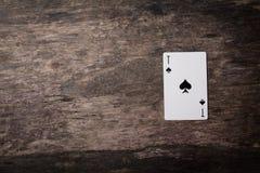 Ás escuro dos cartões de jogo com copyspace na tabela de madeira Imagens de Stock