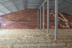 Ático de una casa bajo construcción con el aislamiento en el piso tubos Pared de ladrillo foto de archivo libre de regalías