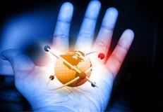 Átomo en la mano foto de archivo