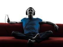 Áudio de escuta da música do treinador do sofá do homem Fotografia de Stock