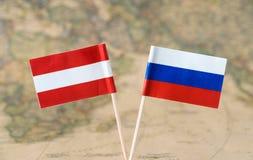 Áustria e Rússia embandeiram os pinos em um conceito do mapa do mundo, as políticas ou as diplomáticas das relações imagem de stock